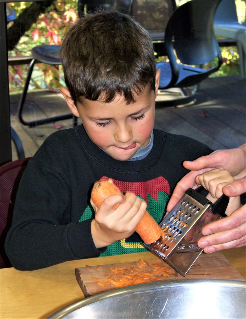 Nevada City School of the Arts students grating an organic, local carrot for carrot cole slaw as part of Tasting Week where about 3,000 elementary school students receive cooking lessons.