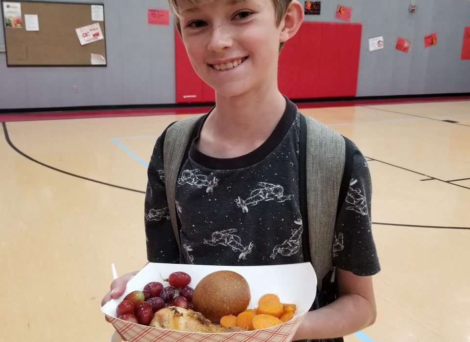 D. Seven Hills student with his California Thursday Lunch featuring Mary's non-GMO chicken drumstick, honey-glazed organic carrots from Super Tuber Farm, organic grapes from Flying V farming collective, and a whole-wheat California roll.