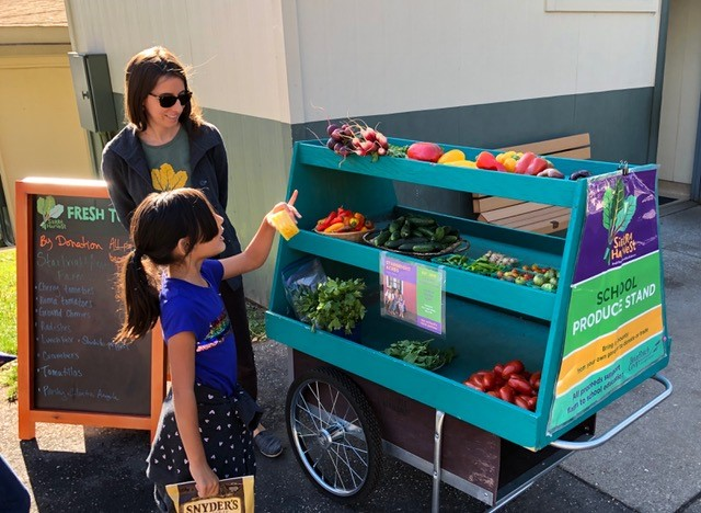 lauren valentino handing out veggies at the farm cart at bell hill school 2019