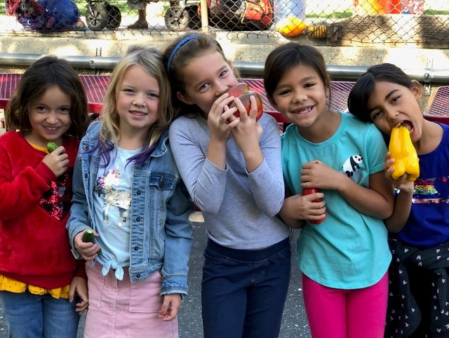 students enjoying fresh veggies at a garden cart at a school 2019
